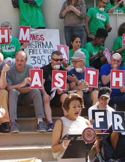 """Protesters at city hall with the words """"Asthma Free"""" behind a speaker"""