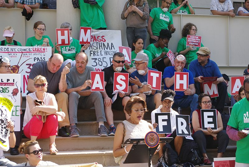 "Protesters at city hall with the words ""Asthma Free"" behind a speaker"