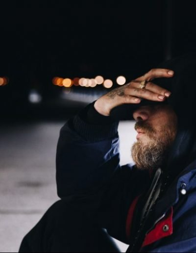 A man sits on a dark sidewalk with his hands over his eyes