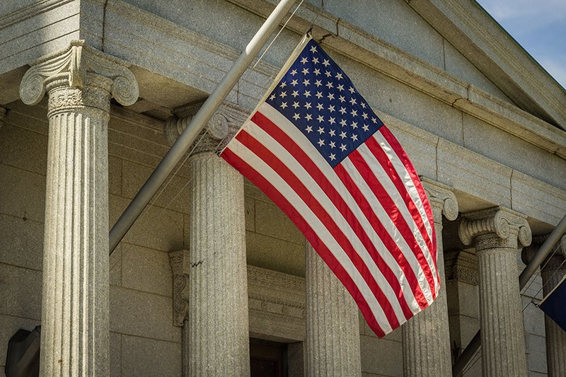 Image shows a courthouse with an American flag outside