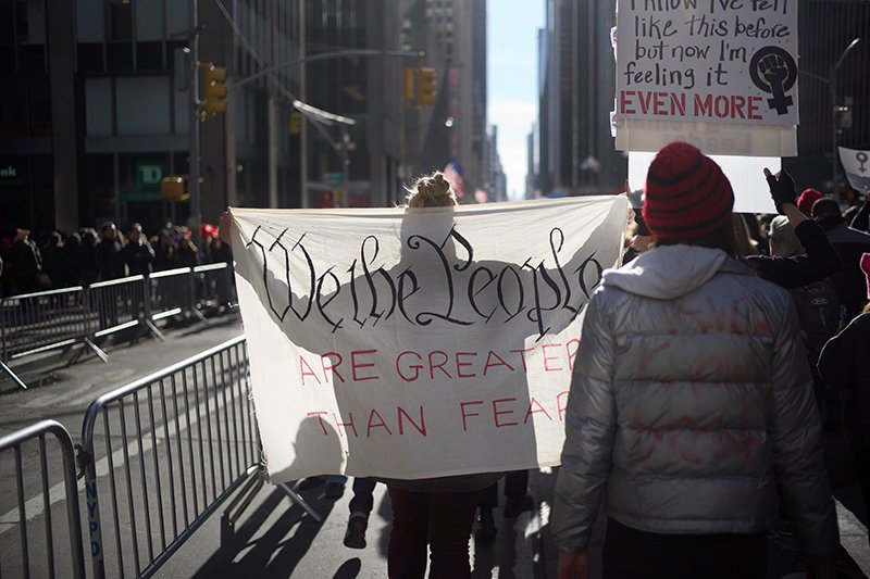 Protesters hold signs quoting the U.S. constitution