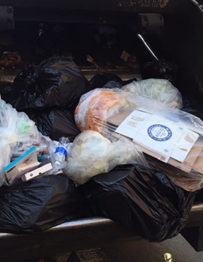 Image shows comingled recycling and trash in the back of a New York garbage truck