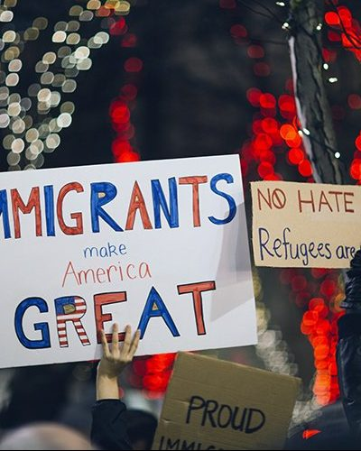 "Image of protestors holding signs saying ""Immigrants make America Great"""