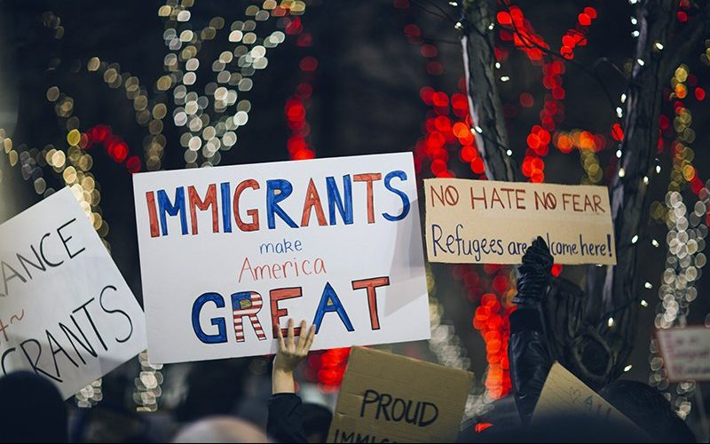 """Image of protestors holding signs saying """"Immigrants make America Great"""""""