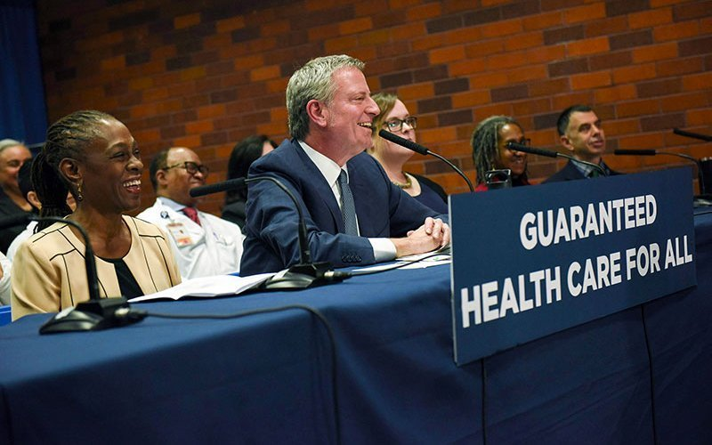 """Image shows Mayor de Blasio announcing """"Guaranteed Health Care for All"""""""