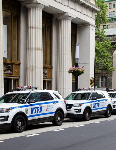 Three New York Police Department vehicles parked in front of a building
