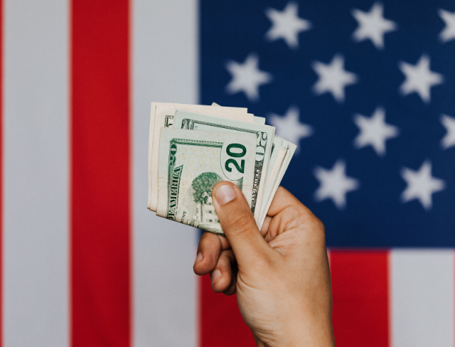 Hand holds money in front of an American flag