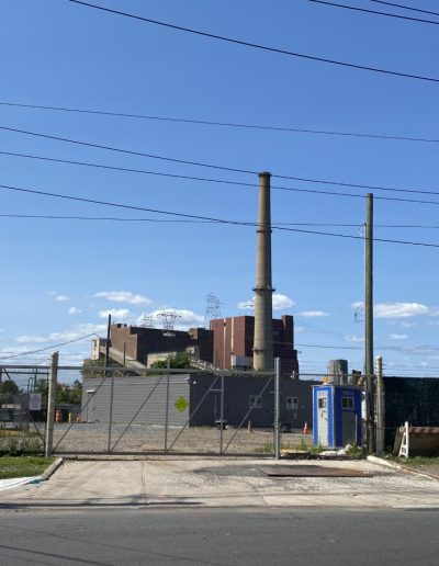 A gray power plant sits in front of a bright blue sky.