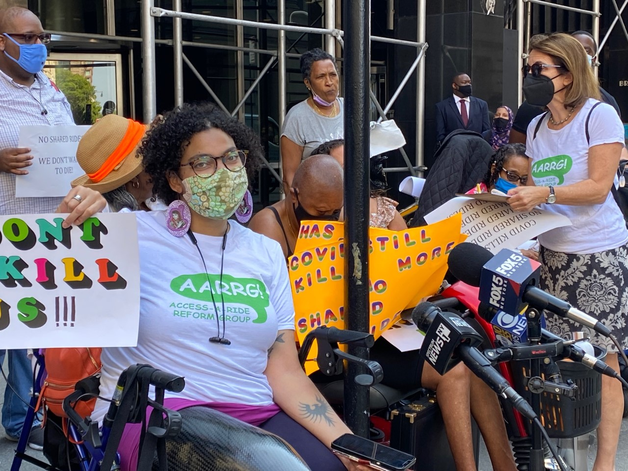 """Eman Rimawi, a Black, Native American and Palestinian woman using a wheelchair, wears a tshirt with the Access-a-Ride Reform Group logo and holds up a sign that reads """"Don't Kill Us."""" She is wearing a mask as other masked protestors gather nearby."""
