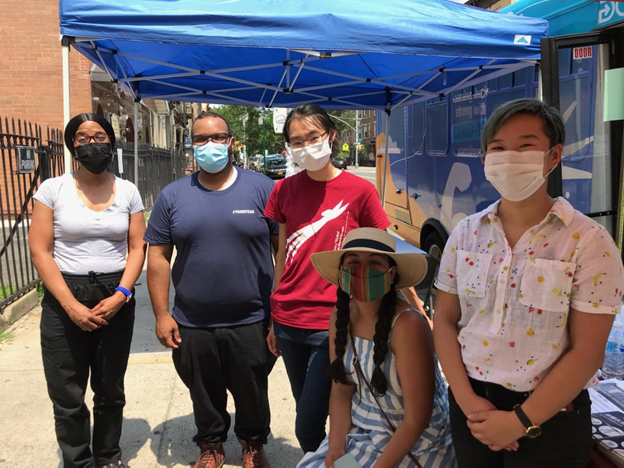 A group of masked volunteers stand in front of a blue pop-up tent outside.
