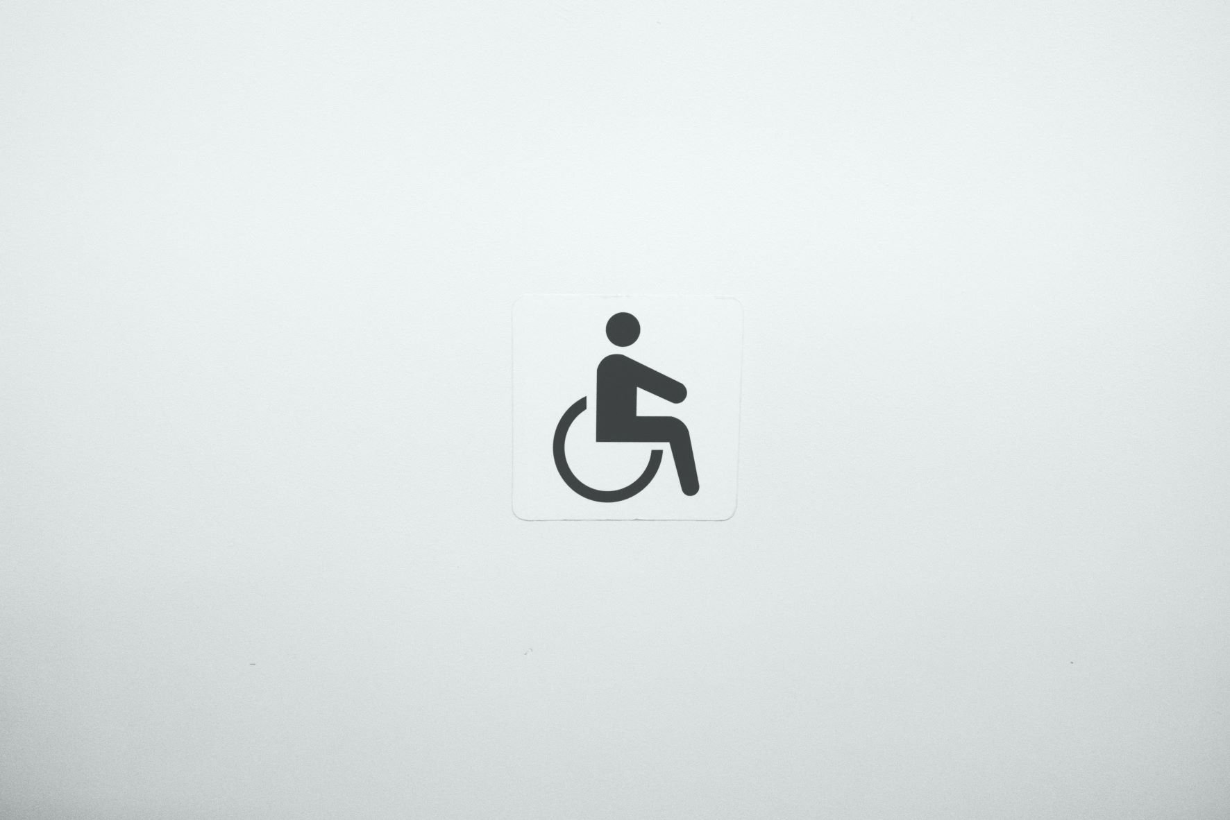 A black symbol of a person in a wheelchair over a white background.