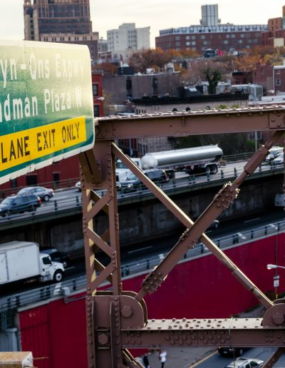 A sign for the Brooklyn-Queens Expressway hangs over an exit filled with semi trucks and taxis.