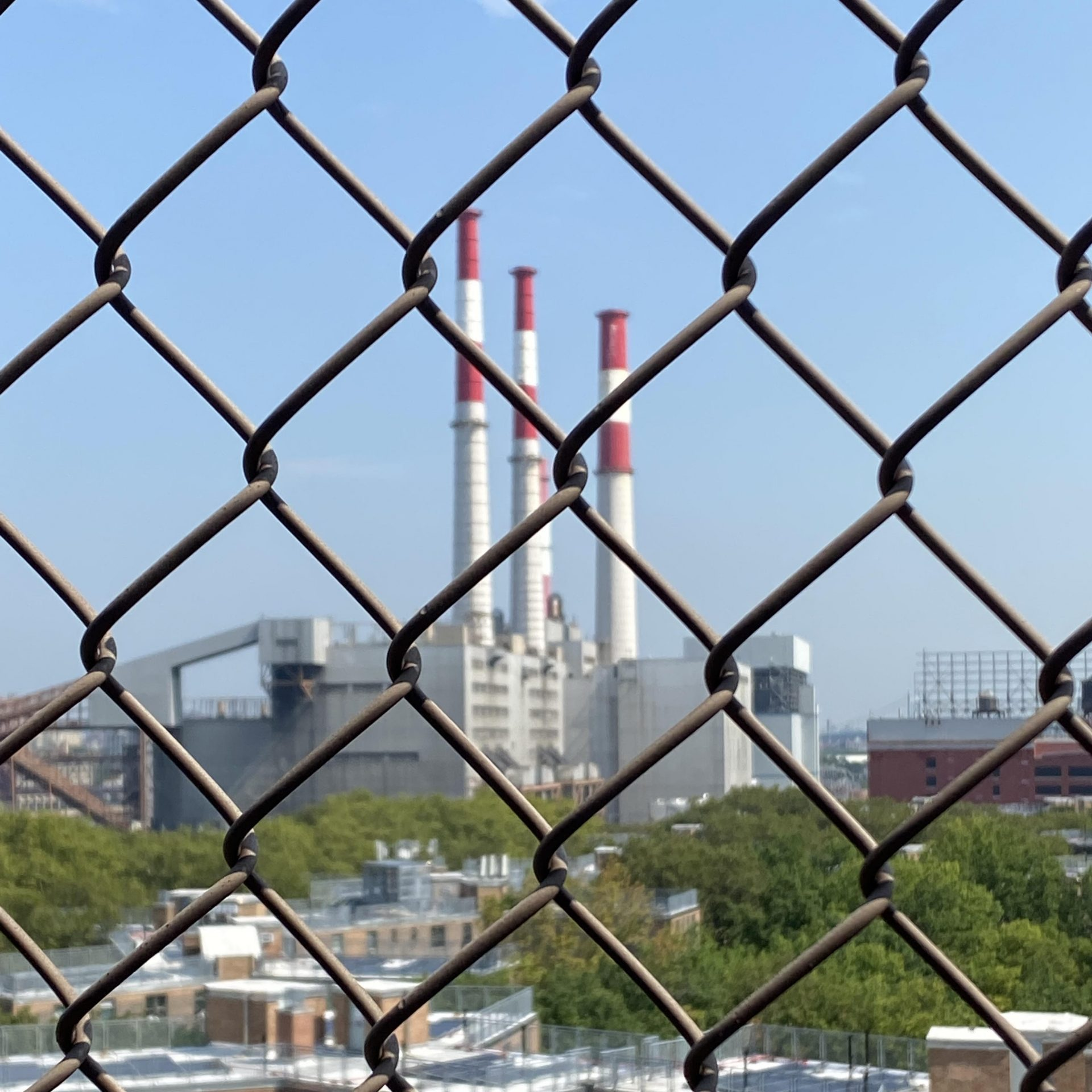 An image of a fossil fuel power plant as viewed through a chain link fence.