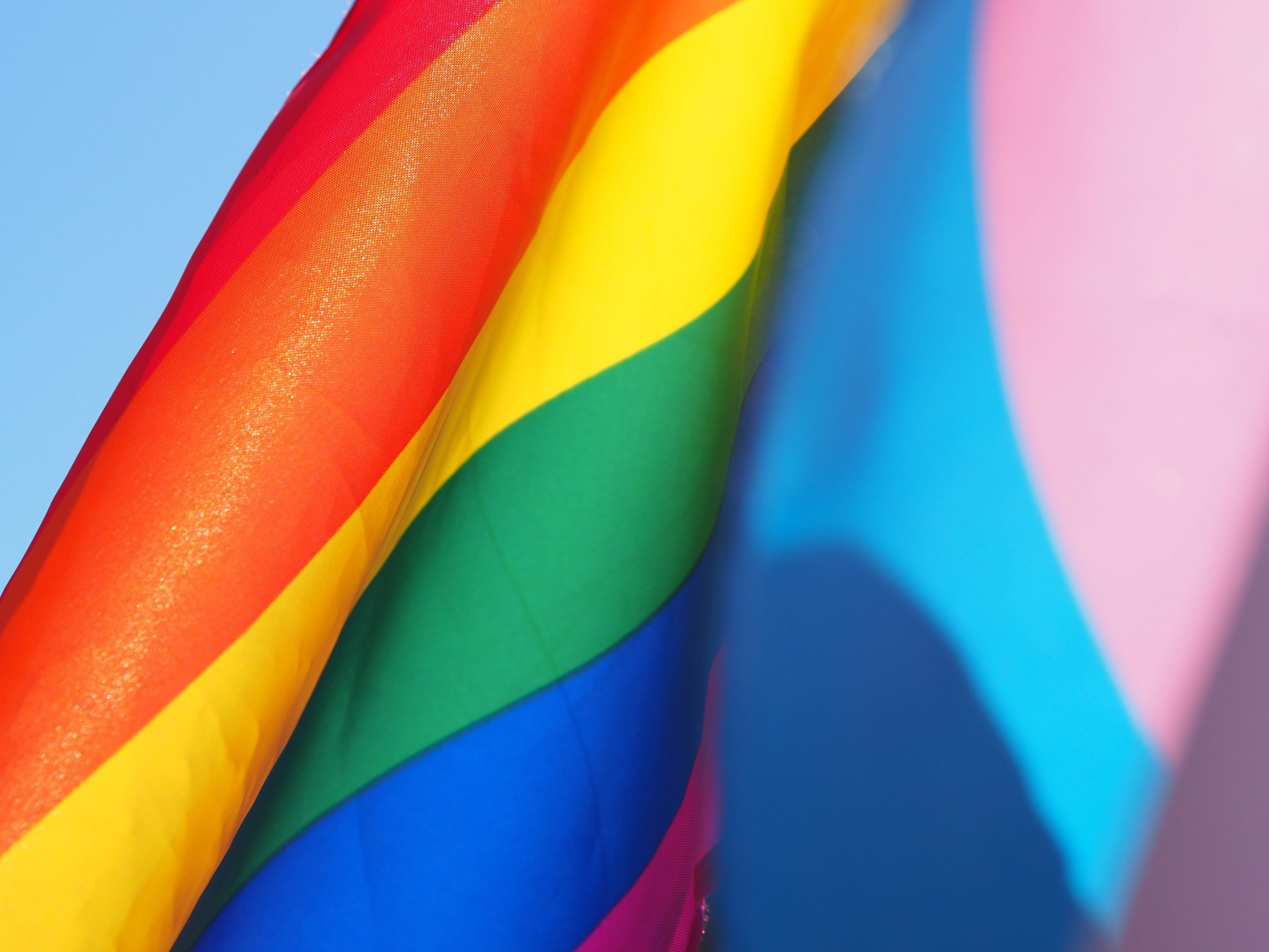 A pride flag featuring the rainbow colors as well as the pink and blue Trans Pride colors.